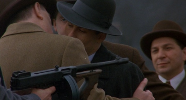 Rocco stands behind Faranzano with a Thompson Mobsters Tommy Gun
